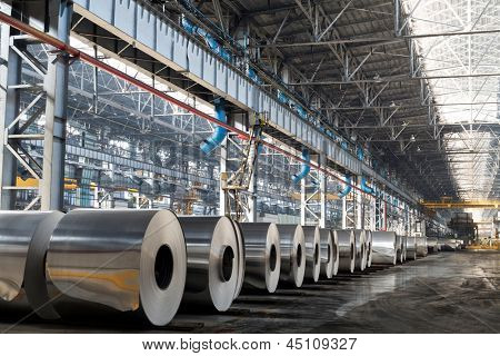 Long row of rolls of aluminum in production shop of plant.