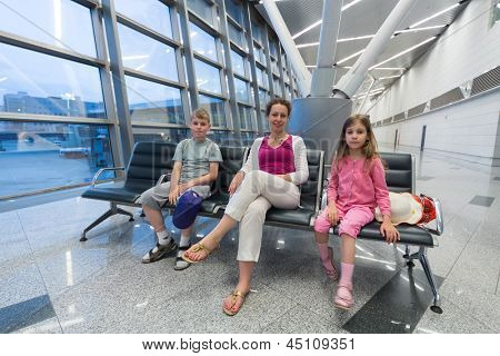 A family of three sitting in a recreation area in the airport  and waiting for boarding
