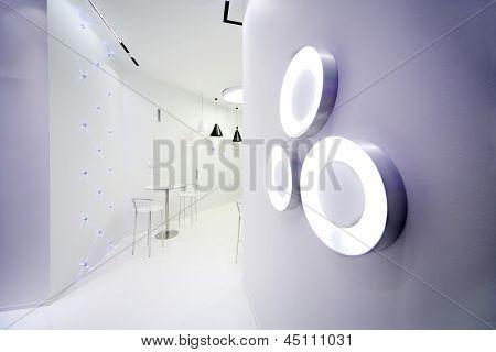 Interior de la cafetería en estilo minimalista, con paredes blancas y tres focos de círculo en la pared.