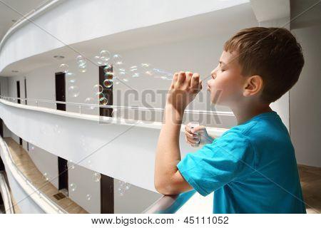 Boy in blue t-shirt lets bubbles on balcony inside large hotel.