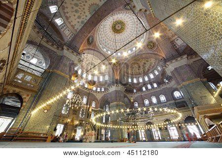 Pessoas no interior da grande, bonita e antiga mesquita nova (Yeni Cami) em Istambul, Turquia. Cúpula central tem