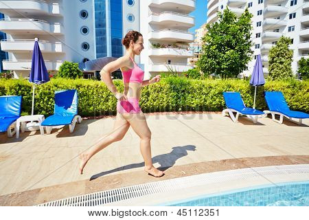 Young smling woman in pink sportswear runs along pool