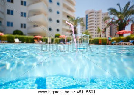Glass with sipper straw floats in pool, low angle view