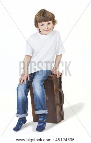White background studio photograph of young happy boy smiling and sitting on a suitcase ready for vacation traveling