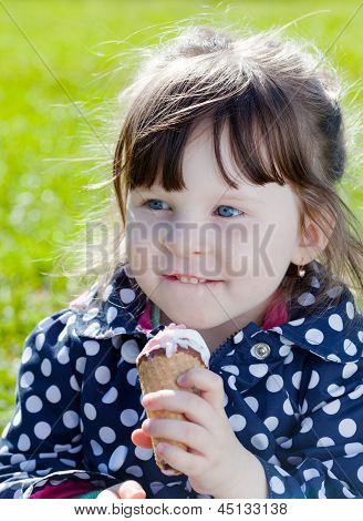 happy girl eats ice cream on the street in spring day
