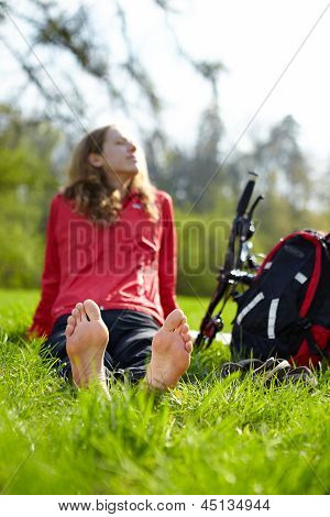 Happy Girl Biker Enjoying Relaxation Sitting Barefoot In Green Grass
