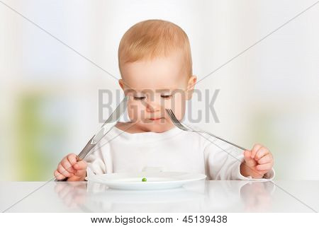 Baby With Fork And Knife Eating, Looking At The Plate With One Pea