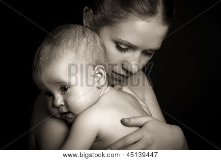 Concept For Love And Family. Mother Hugging Baby Tenderly In Monochrome