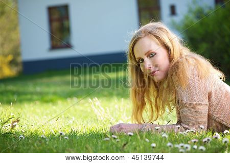 Young Woman Relaxing On Grass Outdoors