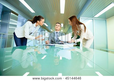 Inspirated boss sitting at workplace surrounded by two secretaries showing him papers
