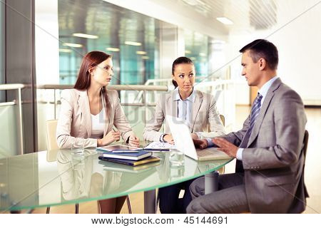 Group of three business partners interacting at meeting in office