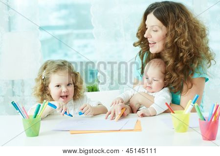 Beautiful mother and her children drawing at home