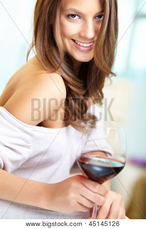 Young beautiful woman with glass of red wine looking at camera