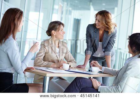四个女企业家在会议上和喝茶交互的形象