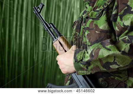 Soldier holding rifle AK-47 against jungle