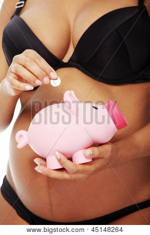 Young beautiful pregnant woman holding a pink piggybank in front of her belly, over a white background.
