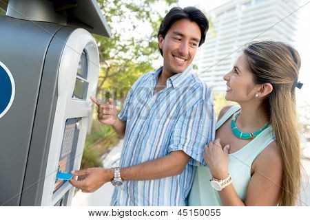 Couple paying for parking with a debit card