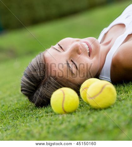 Thoughtful female tennis player lying on lawn