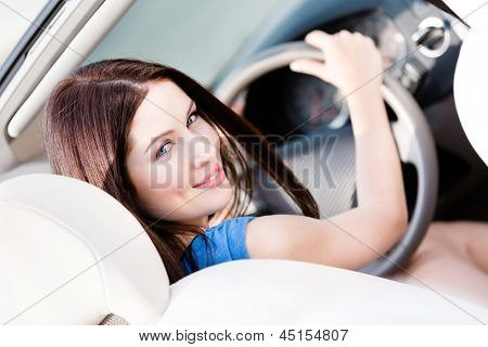 Portrait of pretty female driver turning back