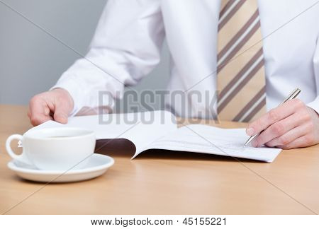 Sitting at the table businessman writing in the notebook