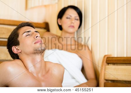 Half-naked man and girl relaxing in sauna. Concept of self-care, health and relaxation