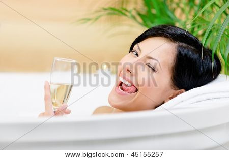 Woman taking a bath with suds drinks champagne, winks and relaxes