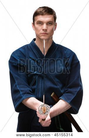 Kendoka in hakama keeps bokken, isolated on white. Japanese martial art of sword fighting