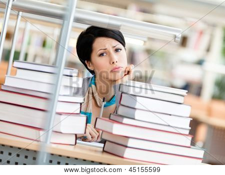 Sad female student is tired of education surrounded with piles of books sitting at the table