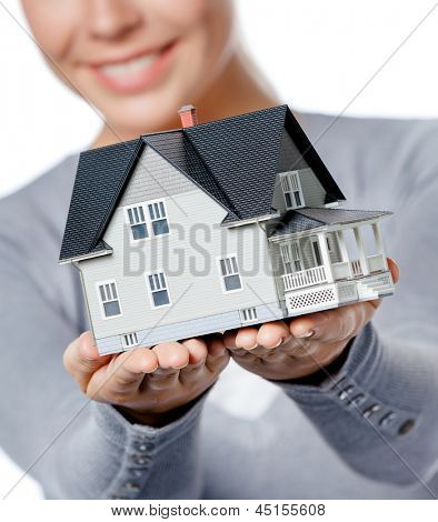 Close up of small model house in female hands, isolated on white