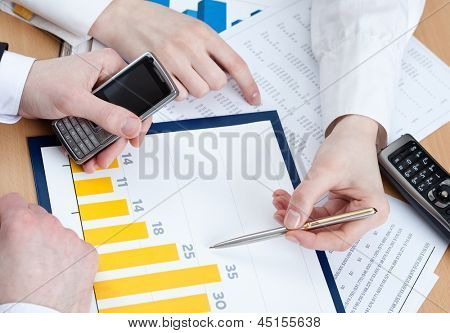 Close up of hands of managers discussing diagram and sitting at the office table with heap of documents