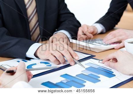 Close up view of hands of managers discussing diagram and sitting at the table with heap of documents