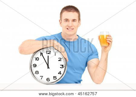 Handsome guy holding a wall clock and glass of orange juice on a table isolated on white background