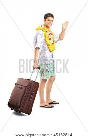 Full length portrait of a smiling man carrying his luggage and waving goodbye isolated on white background