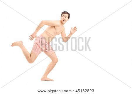 An embarrassed naked man in underwear running away isolated on white background