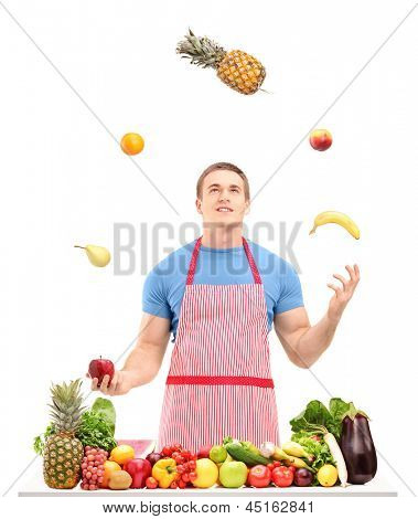Man juggling with fruits behind a table full of fruits and vegetables, isolated on white background