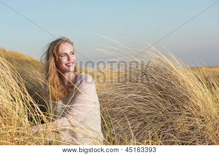 Young Woman Sitting In The Dunes With Long Grass