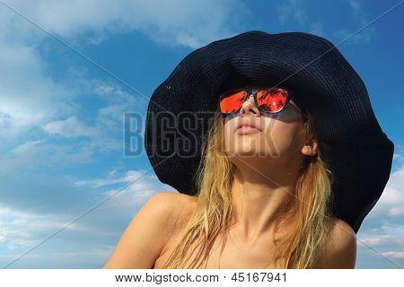 Beautiful young woman in bikini on the beach with palmtree reflection in the sunglasses