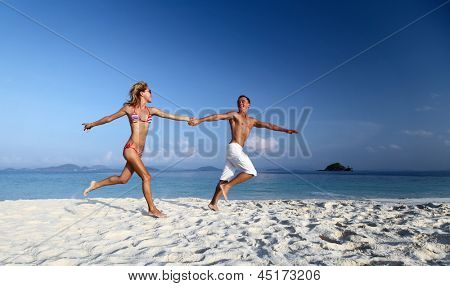Active couple running on a white sandy beach with blue sky on the background