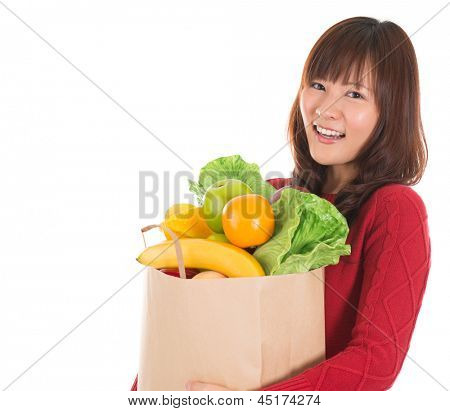 Happy smiling young Asian woman holding paper shopping bag full of groceries isolated on white