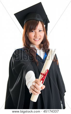 Portrait of smiling Asian female student in graduate gown showing graduation diploma isolated on white background