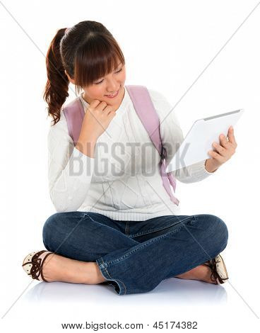 Full body Asian female young adult student sitting on floor using tablet pc isolated on white background