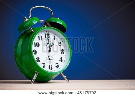 Große grüne Wecker auf dunkel blauem Hintergrund