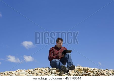 Young casual man working with touch pad at the beach