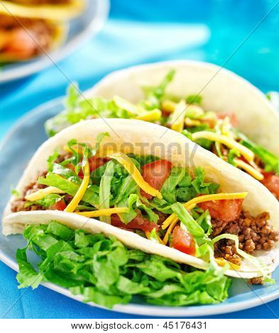 Mexican food - Soft shell tacos with beef, cheese, lettuce and tomatoes