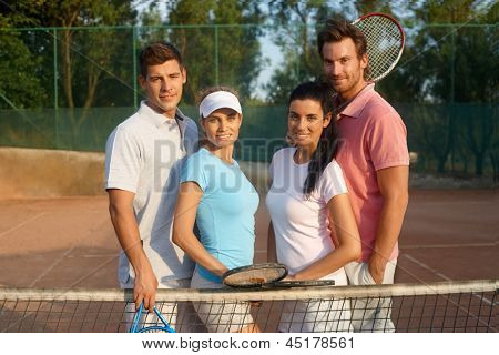 Young couples standing on tennis court, smiling.