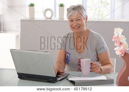 Senior woman working on laptop computer, looking at camera, drinking tea.
