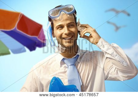 Happy young businessman on summer holiday listening to murmur of sea in seashell.