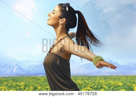 Attractive young woman enjoying summer sun and wind on the meadow. Side view, pretending to fly.