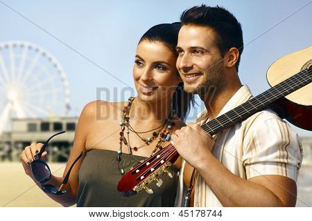 Summer portrait of happy smiling loving couple standing on the coast, man holding guitar.