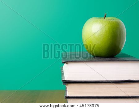 Green apple on a pile of book, isolated on green background